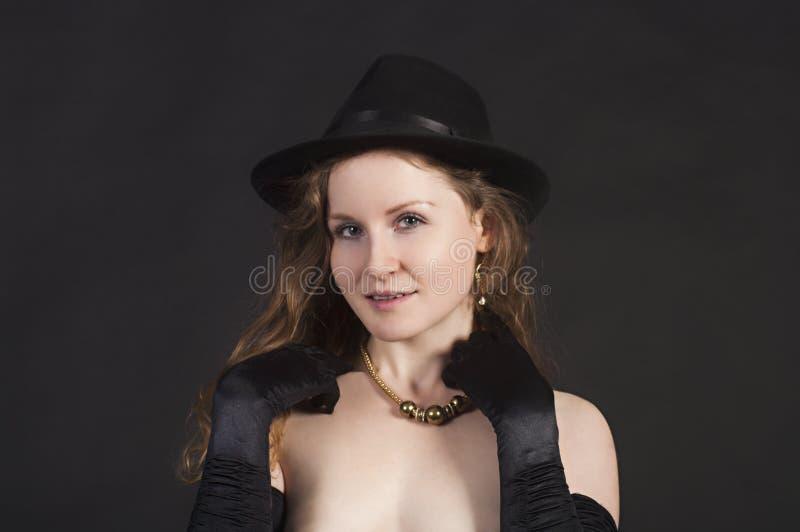 Portret van een jonge vrouw in een hoed en handschoenen stock fotografie