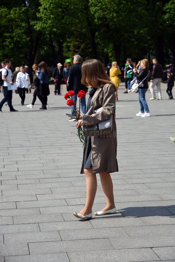 Portret van een jonge vrouw houdt zij rode anjers stock foto