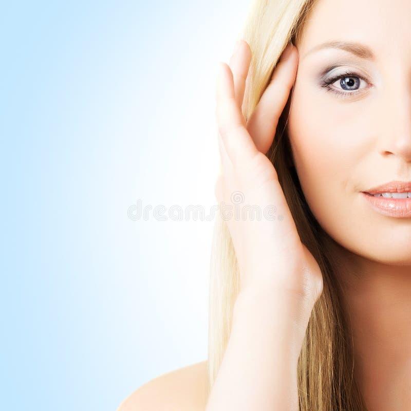 Portret van een jonge vrouw in make-up op een blauwe achtergrond royalty-vrije stock fotografie
