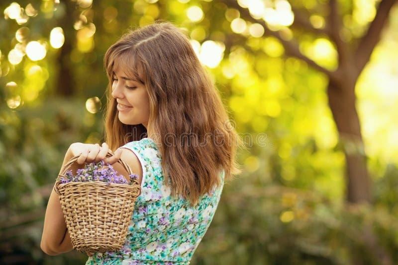 Portret van een jonge vrouw met een mand van bloemen stock foto's