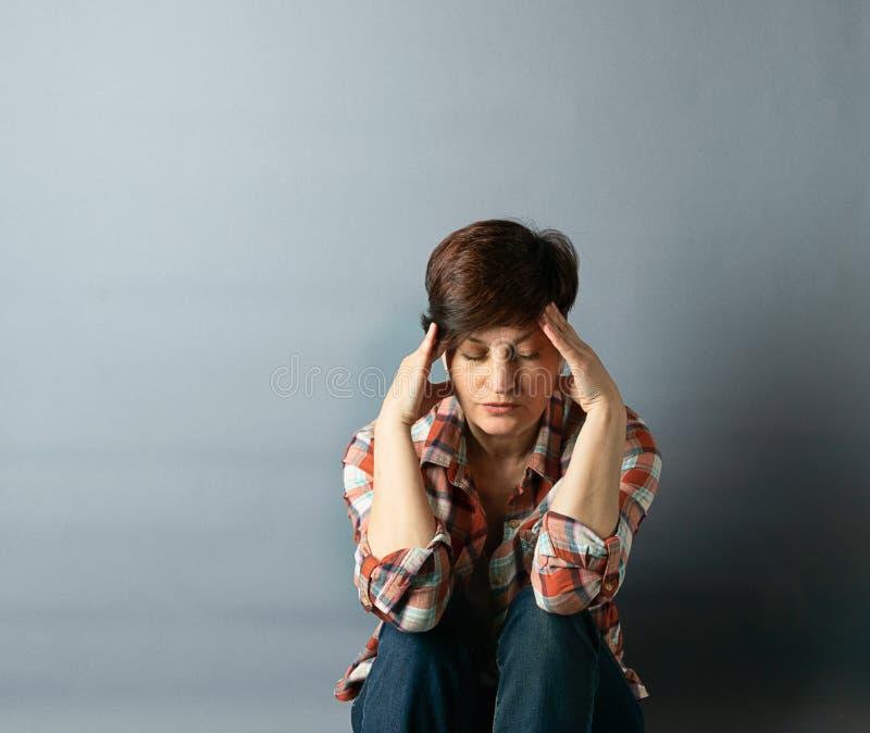 Portret van een jonge vrouw met een kort kapsel dat tegen de muur op grijze lege achtergrond zit Menselijke emoties stock afbeelding
