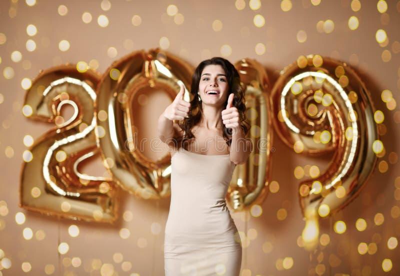 Portret van een jonge vrouw in naakte kleding s onder boke die Pret met de Gouden Ballon van 2019 hebben stock afbeelding