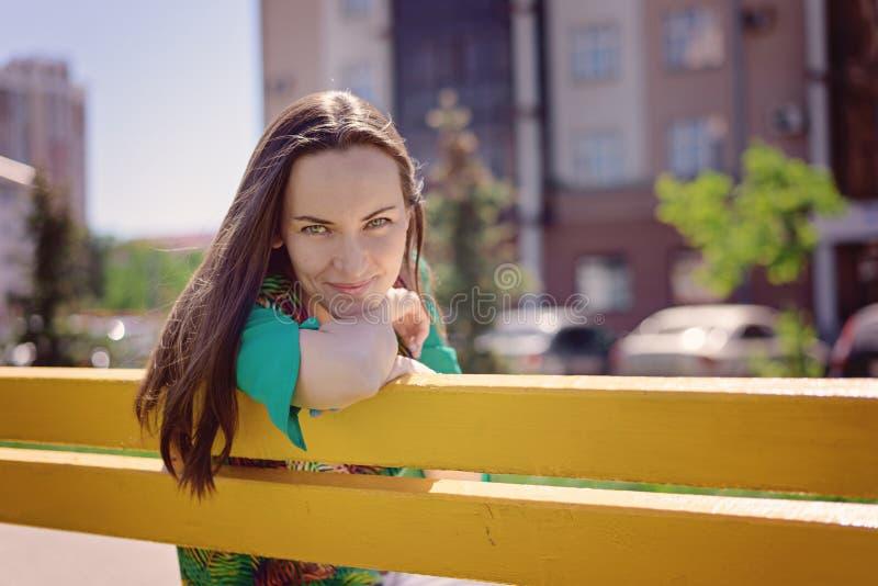 Portret van een jonge vrouw op een gele bank, het glimlachen het bekijken de camera, exemplaarruimte stock foto's