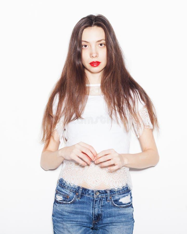 Portret van een jonge vrouw in een in uitrusting Het stellen in de studio op een witte achtergrond Helder samenstelling en kapsel stock foto's
