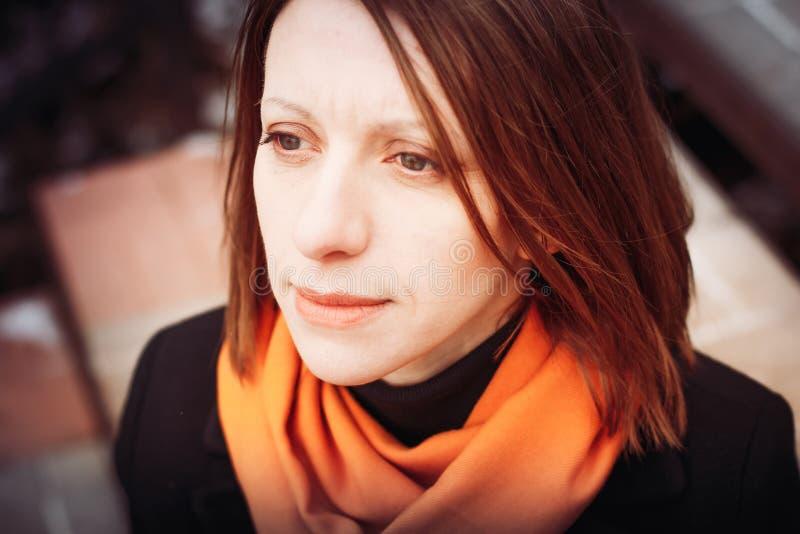 Portret van een jonge vrouw in een zwarte laag en rode sjaal in de stad stock afbeeldingen