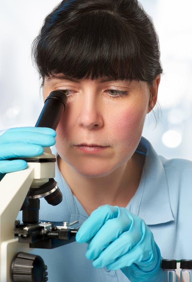 Portret van een jonge vrouwelijke wetenschapper die met microscoop werken royalty-vrije stock afbeeldingen