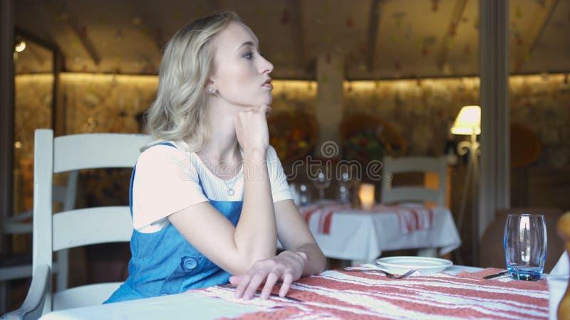 Portret van een jonge zitting van de blondevrouw op keuken thuis Art Jonge aantrekkelijke blondezitting in de keuken stock afbeeldingen