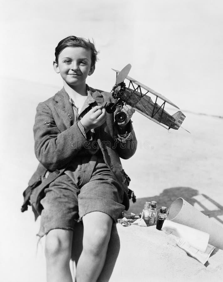 Portret van een jongen die een modelvliegtuig houden en (Alle afgeschilderde personen langer glimlachen leven niet en geen landgo stock afbeelding
