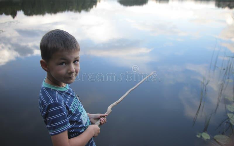 Portret van een jongen die in meer vissen die op de hemel wijzen stock foto