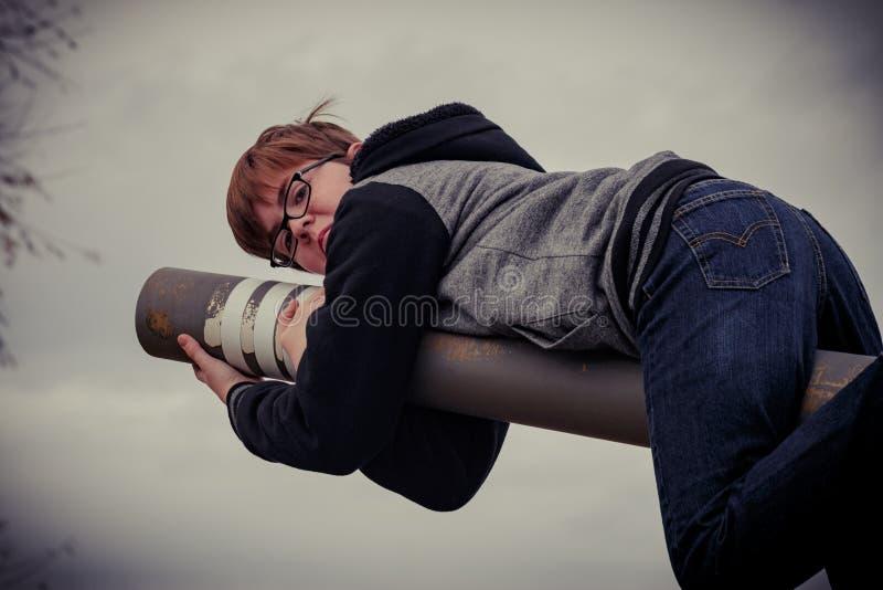 Portret van een Jongen die zich aan Rusty Pole vastklampen stock foto's