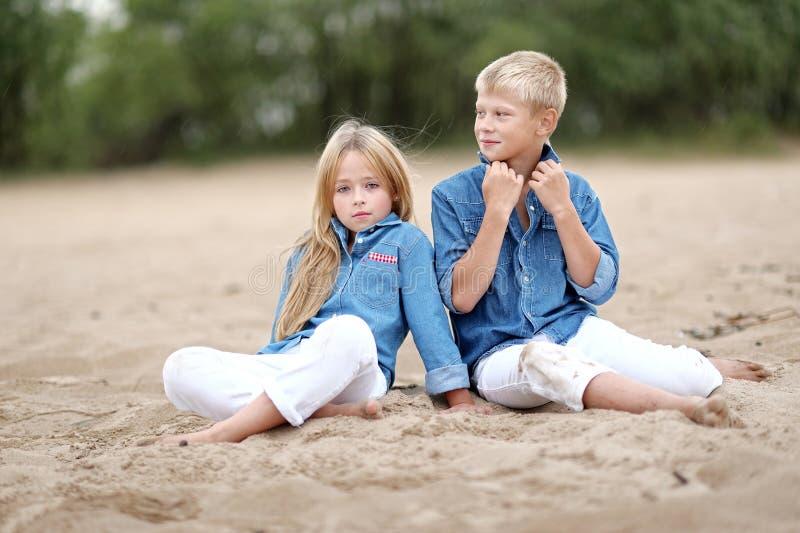Portret van een jongen en een meisje op het strand stock afbeeldingen