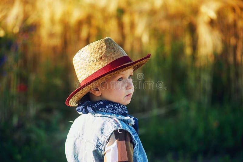 Portret van een jongen in een strohoed, de stijl van het land stock foto's