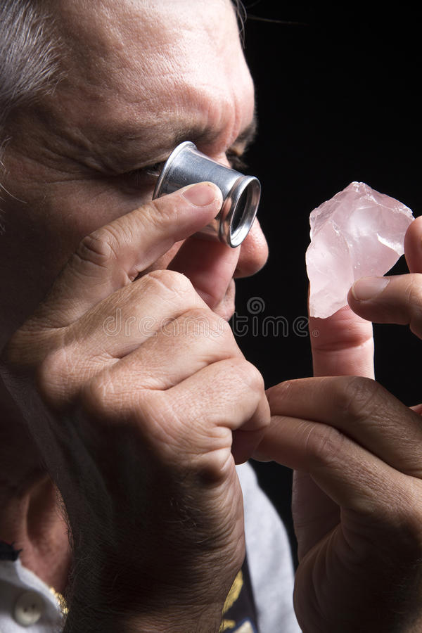 Portret van een juwelier tijdens de evaluatie van juwelen stock fotografie