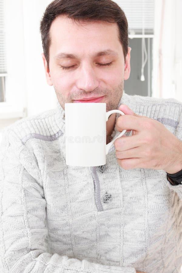 Portret van een kalme mens die een koffie in zijn woonkamer hebben royalty-vrije stock fotografie