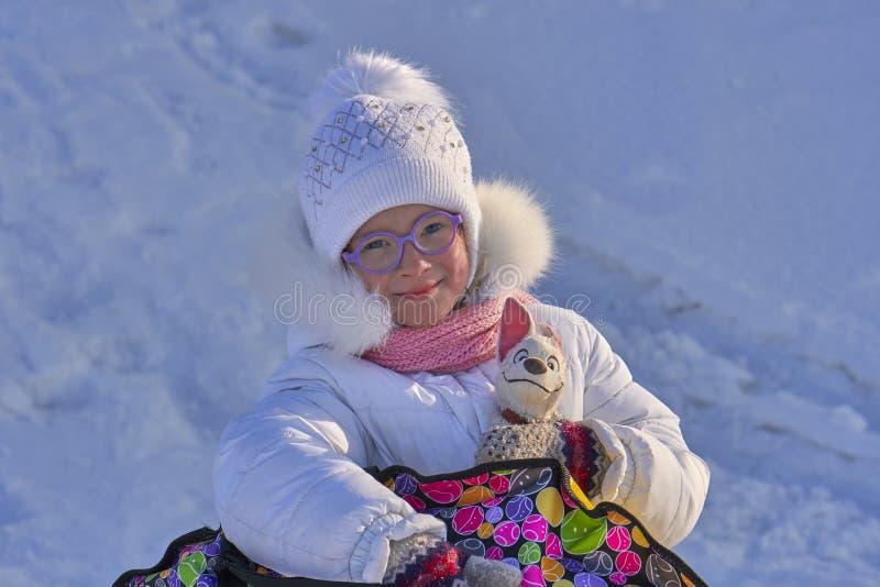 Portret van een kindmeisje in glazen op een zonnige de winterdag Het meisje rolde op de slee van de heuvel Zij houdt het sleebuiz stock fotografie