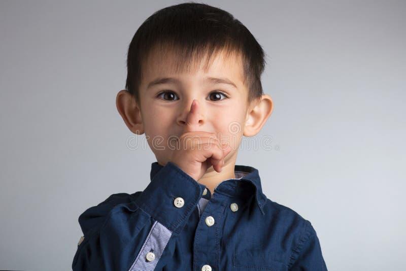 Portret van een klein grappig jongensgezicht die een vingergebaar tonen: qui royalty-vrije stock fotografie