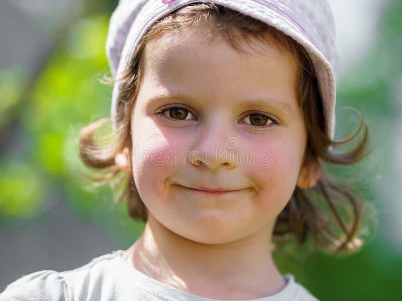 Portret van een klein Kaukasisch meisje met een hoed die tegen de ruwe zon beschermen Groene onduidelijk beeldachtergrond royalty-vrije stock foto's