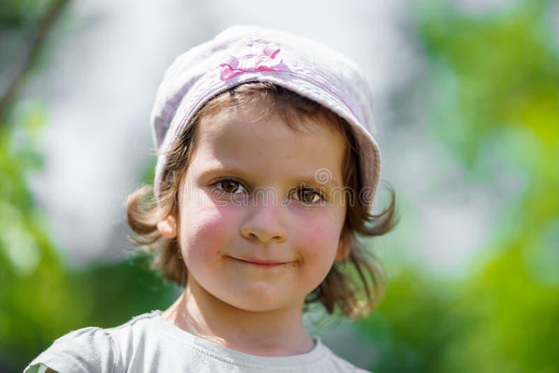 Portret van een klein Kaukasisch meisje met een hoed die tegen de ruwe zon beschermen Groene onduidelijk beeldachtergrond royalty-vrije stock foto