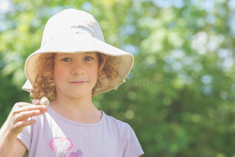 Portret van een klein Kaukasisch meisje met een hoed die tegen de ruwe zon beschermen Groene onduidelijk beeldachtergrond stock foto
