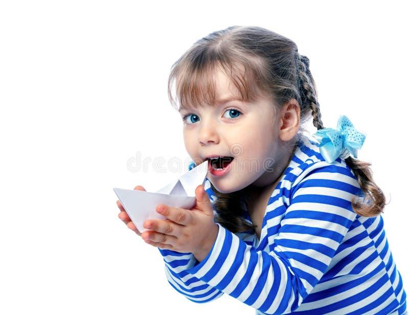 Portret van een klein meisje die een document boot op een witte backgr houden stock fotografie