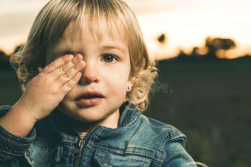 Portret van een klein meisje die haar oog behandelen met één hand stock afbeelding