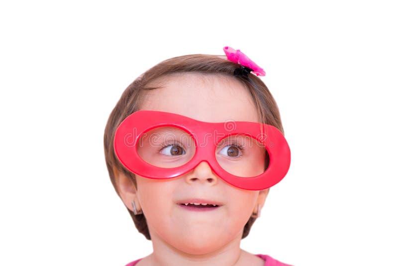 Portret van een klein meisje die rode plastic stuk speelgoed oogglazen dragen stock afbeeldingen