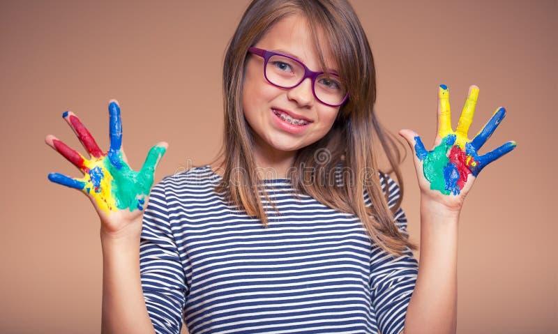 Portret van een klein meisje die van de pre-tienerstudent geschilderde handen tonen Gestemde foto stock foto's