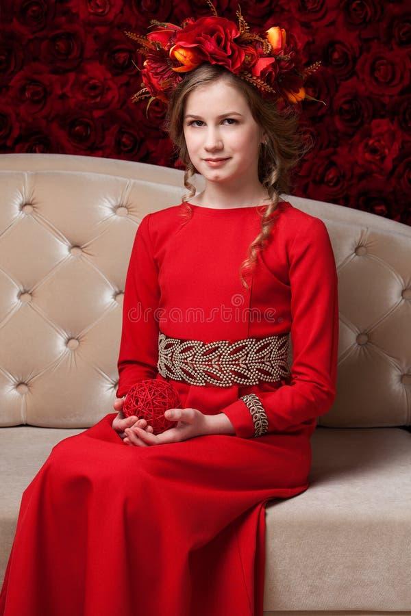 Portret van een klein meisje in een bloemkroon en een rode kledingssitti stock fotografie