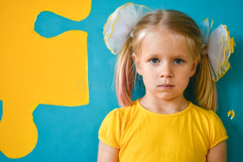 Portret van een klein meisje in gele kleding op een gele en blauwe achtergrond met een raadsel royalty-vrije stock foto
