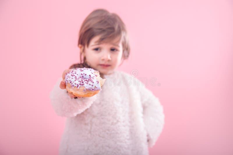 Portret van een klein meisje met een doughnut in haar handen royalty-vrije stock foto
