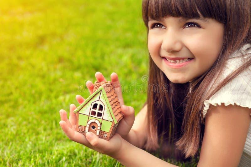 Portret van een klein meisje met huis in hand op een achtergrond van royalty-vrije stock afbeeldingen