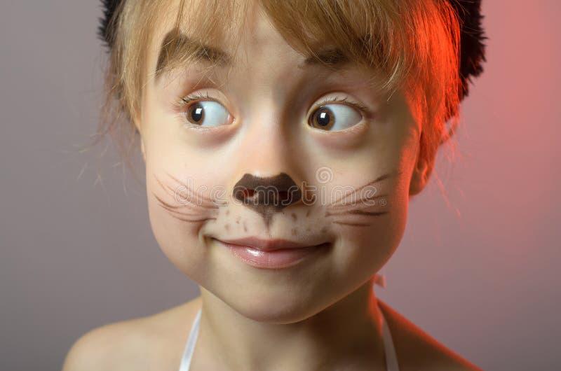 Portret van een klein meisje met kattensamenstelling op een grijze achtergrond royalty-vrije stock afbeeldingen