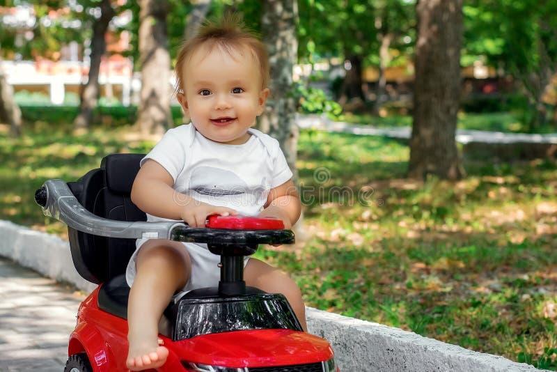 Portret van een kleine bestuurder: gelukkig zuigelingskind met verraste gezichtszitting blootvoets op een rode duwauto openlucht  stock afbeelding