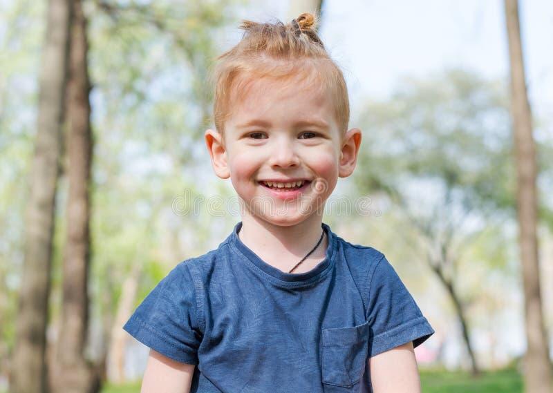 Portret van een kleine jongen die in het park in de lente lacht royalty-vrije stock fotografie