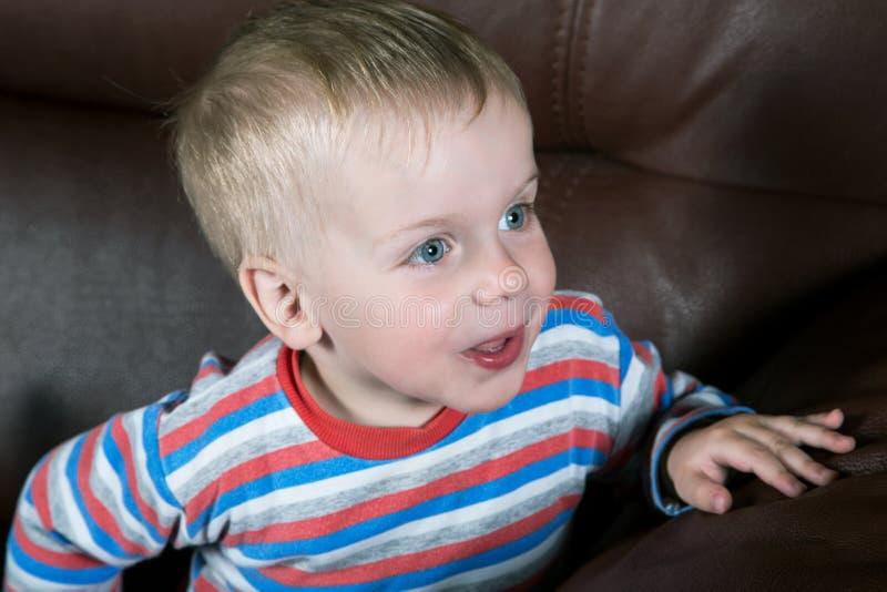 Portret van een kleine jongen op een leerbank royalty-vrije stock foto