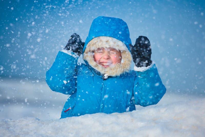 Portret van een kleine jongen in openlucht in de sneeuw stock foto's