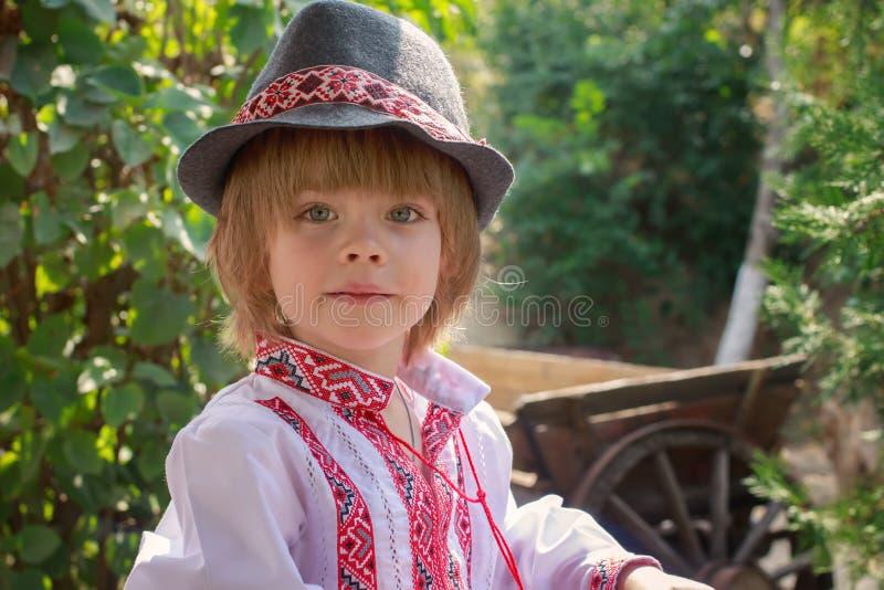Portret van een kleine jongen in een wit geborduurd overhemd en een hoed royalty-vrije stock fotografie