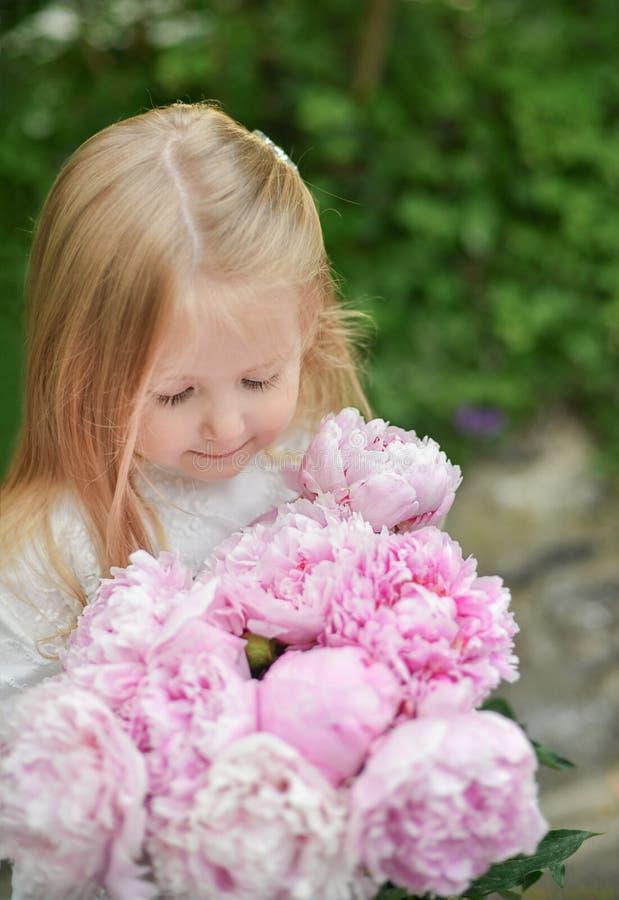 Portret van een kleine meisjes ruikende pioenen royalty-vrije stock fotografie