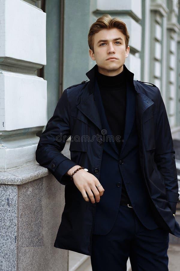 Portret van een knappe, aantrekkelijke, jonge mens in een blauw kostuum, laag, in de stad peinzend en droevig, het wachten royalty-vrije stock fotografie
