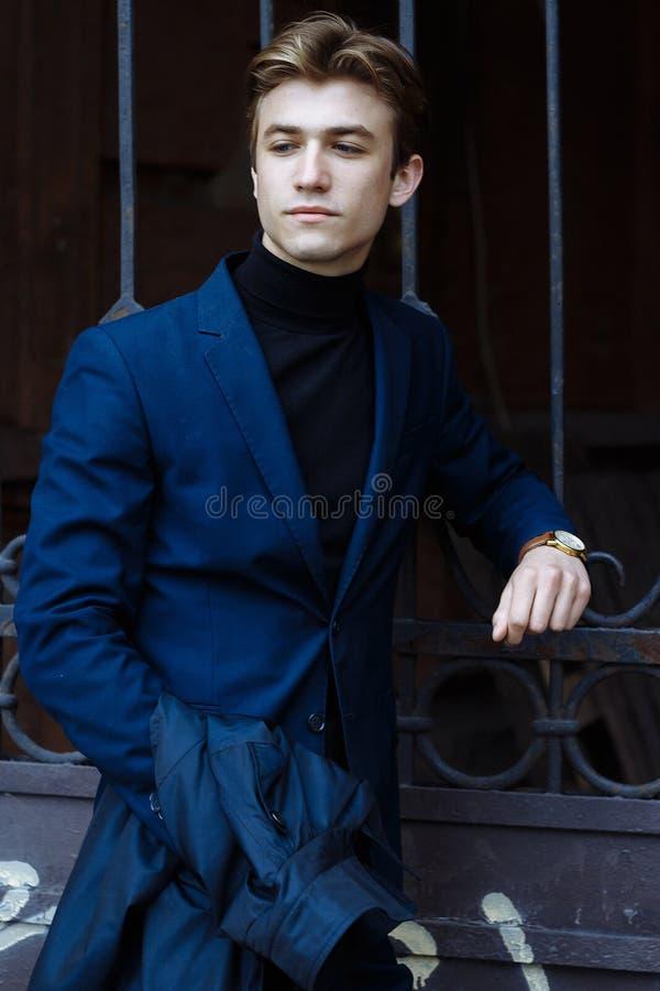 Portret van een knappe, aantrekkelijke, jonge mens in een blauw kostuum, laag, in de stad peinzend en droevig, het wachten royalty-vrije stock afbeeldingen
