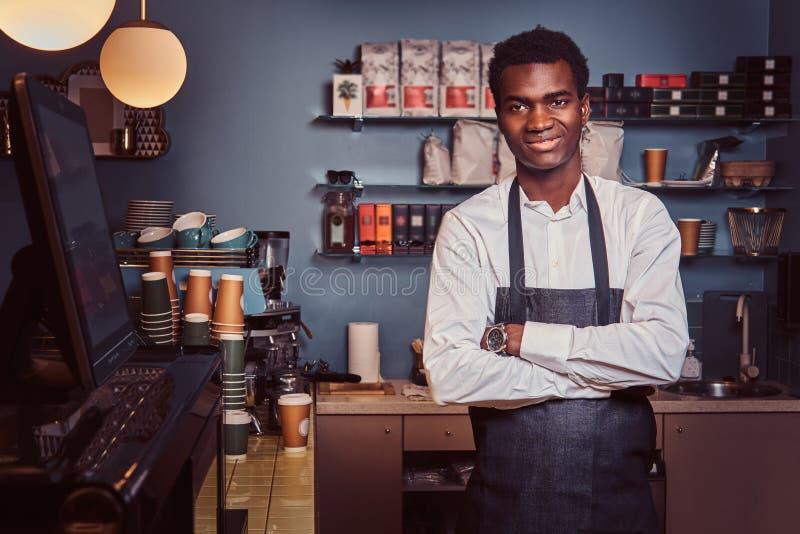Portret van een knappe Afrikaanse barista die zich met gekruiste wapens bevinden bij teller van een in koffiewinkel stock foto
