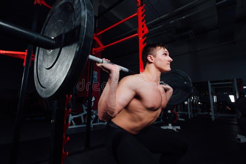 Portret van een knappe atleet bij gymnastiek de mens doet de oefening met barbell, status en het hurken grote zeker stock foto