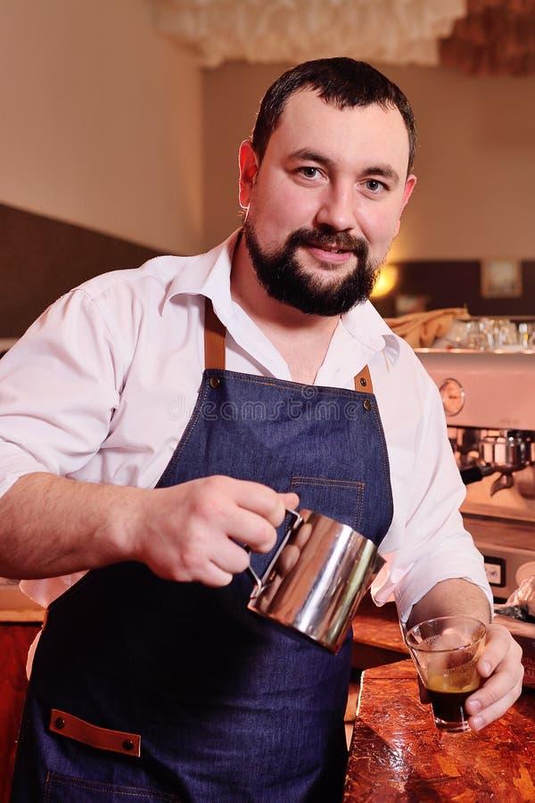 Portret van een knappe gebaarde barista die koffie op de achtergrond van een koffiehuis voorbereiden royalty-vrije stock foto