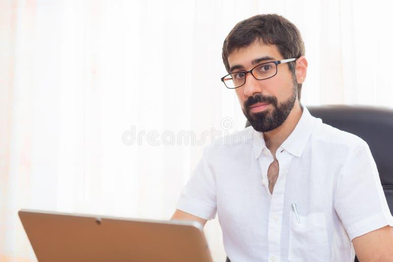 Portret van een knappe hipsterkerel die op het kantoor werken royalty-vrije stock afbeeldingen