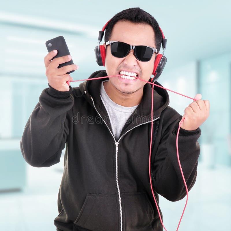 Portret van een knappe jonge mens die aan muziek luisteren royalty-vrije stock afbeeldingen