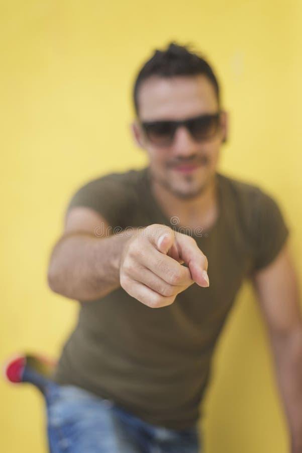 Portret van een knappe jonge mens die vinger richten op u tegen stock foto