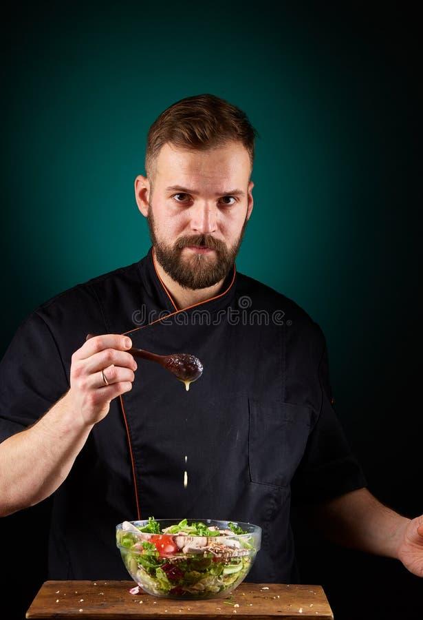 Portret van een knappe mannelijke chef-kokkok die smakelijke salade op een vage aquamarijnachtergrond maken stock foto