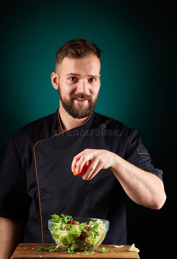 Portret van een knappe mannelijke chef-kokkok die smakelijke salade op een vage aquamarijnachtergrond maken royalty-vrije stock afbeelding