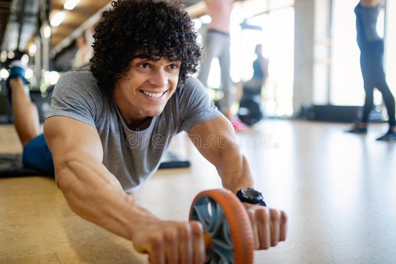 Portret van een knappe mens die duwups oefening in gymnastiek doen stock foto