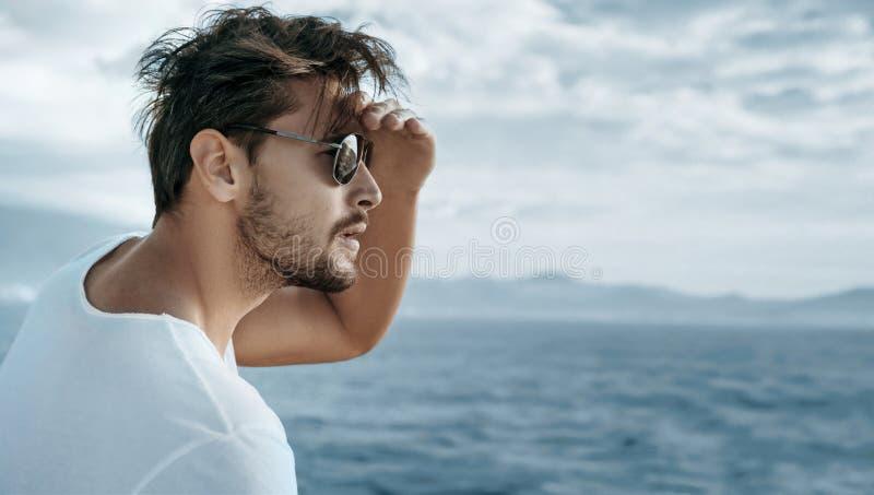 Portret van een knappe mens die op oceaangolven letten royalty-vrije stock foto